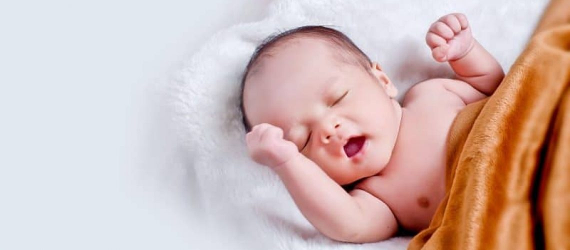 baby-lying-on-white-fur-with-brown-blanket-1973270